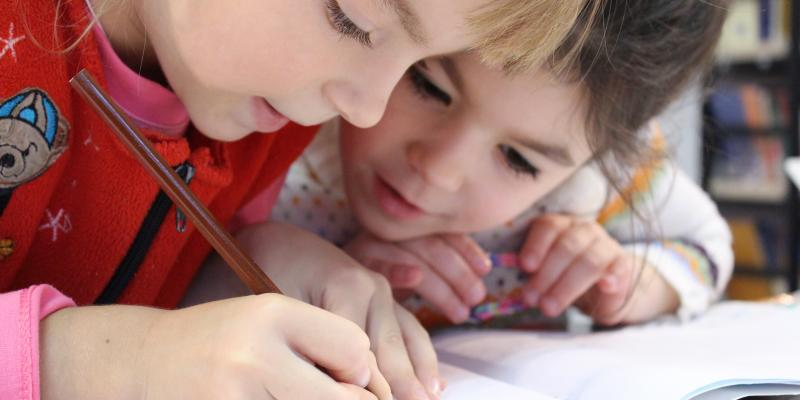 2 kids reading a book and writing together