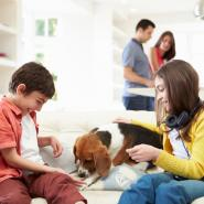 two kids and a dog sitting on the couch with two parents in the kitchen behind them